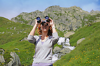 Girl with binoculars in ALpine mountains