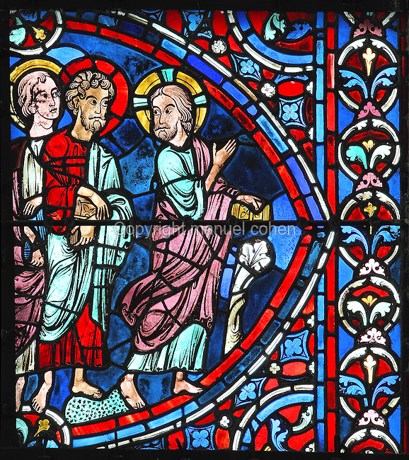 Two new disciples have left John the Baptist to follow Jesus, who, turning back to them, indicates the correct path with a broad gesture of his right hand. Section of two disciples following Christ, from the Apostles window, 1212-25, in the axial chapel in the ambulatory of Chartres Cathedral, Eure-et-Loir, France. This window represents the birth of the Church, as the apostles are the first pillar of the church and therefore has the site with the most sunlight to illuminate the colours. Chartres cathedral was built 1194-1250 and is a fine example of Gothic architecture. Most of its windows date from 1205-40 although a few earlier 12th century examples are also intact. It was declared a UNESCO World Heritage Site in 1979. Picture by Manuel Cohen