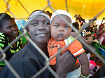 A mother and her child look through a fence during a Catholic Mass on Easter morning, April 5, inside a United Nations base in Juba, South Sudan, where some 34,000 people have sought protection since violence broke out in December 2013. More than 112,000 people currently live on UN bases in the war-torn country, most of them afraid of tribally targeted violence. The Catholic Church has maintained a pastoral presence inside the camps.