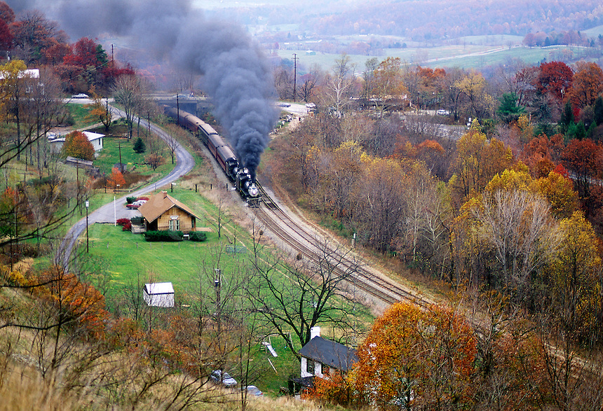 Virginia Central Railroad steam train puffing a cloud of black smoke through an idyllic scene of fall foliage in the mountains.#7011. Virginia.
