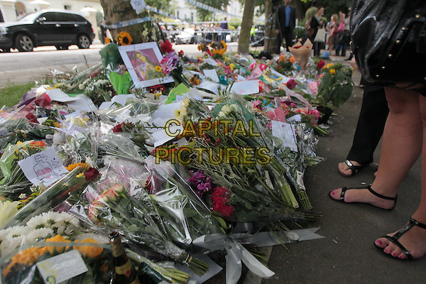 Fans leave tributes outside Amy Winehouse's house in Camden Square, London, England. The 27 year old singer was found dead in her London home on Saturday 23rd July..July 24th, 2011.atmosphere gv general view death flowers cigarettes wine drink beverage pictures photographs candles  feet.CAP/HIL.©John Hillcoat/Capital Pictures .