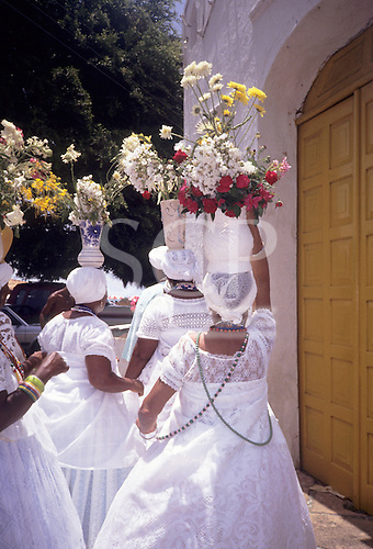 Itaparica Island, Bahia, Brazil. Baiana women outside the church with vases of flowers on their heads dressed in white.