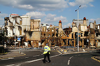 A policeman walks towards the completely burnt out and destroyed Reeves furniture store next to other burnt out buildings in the London borough of Croydon. London saw the beginnings of riots on Saturday evening, after a peaceful protest in response to the shooting by police of Mark Duggan during an attempted arrest, escalated into violence. By the third night of violence, rioting and looting had spread to many areas of the capital and to other cities around the country.