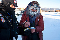 Volunteer veterinarian Michael Walker has musher Michelle Phillps sign her vet book at the Kaltag checkpoint during the 2010 Iditarod