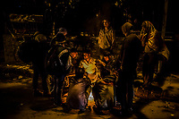 OLD DELHI, INDIA, JANUARY 12, 2016: Men sit around a fire, near to a sleep market on January 12, 2016 in Old Delhi, India. <br /> Daniel Berehulak for The New York Times