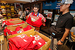A staff member gives a Hiroshima Carp Central League Champions 2016 t-shirt to a fan at Hiroshima Brand Shop TAU in Ginza on September 11, 2016, Tokyo, Japan. Hundreds of Carps fans lined up from early morning outside Hiroshima Brand Shop TAU to buy victory t-shirts after Hiroshima baseball team got its first Central League title in 25 years after beating the Yomiuri Giants 6-4 on Saturday, September 10. (Photo by Rodrigo Reyes Marin/AFLO)