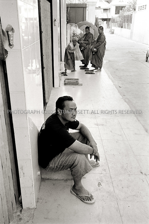 12/2/2007--Phnom Penh, Cambodia..Hin Roatnak, aka Cobra, a former Crip from central California, who says he was deported for a gang murder, hangs out in the 'hood while Buddhist monks (behind) collect alms from Cambodian neighbors. Tired of trouble in his life, Cobra has settled down with his wife and works for Tiny Toones, a small NGO that teaches at risk Cambodian kids how to break dance, in order to keep them off the streets. One of Cobra's jobs is teaching English to the kids, most of whom are from very poor families, thereby using one of the few skills the deportees all have?speaking English...©2007 Stuart Isett. All rights reserved©2007 Stuart Isett. All rights reserved
