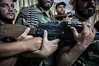 "Members of a rebel faction of the FSA at Ibeen town hold a machine gun inside a security house as they show the weaponry they have to protect the so called ""liberated territory""."