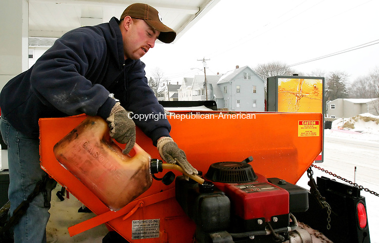 TORRINGTON, CT. 14 February 2007--021407SV05--Bob Scanlon of Colonial Landscaping fills the motor on his truck sander at 12 noon in Torrington Wednesday. Scanlon had been plowing and sanding his accounts since 12 midnight and after 12 hours wasn't planning to stop anytime soon.<br /> Steven Valenti Republican-American