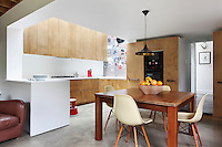 The kitchen/dining room with a bespoke kitchen made with birch face cabinet doors by Mick Coates. The chairs at the table are reproduction Charles Eames DSW chairs