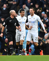 Swansea City's Jack Cork (centre) and Swansea City's Gylfi Sigurdsson (right) speak with Referee Mike Dean (left) as Manchester City's Gabriel Jesus scores the second goal during the Premier League match between Manchester City and Swansea City at the Etihad Stadium, Manchester, England. Sunday 05 February 2017