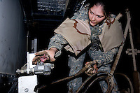Private First Class Brenneis,  with Echo Company, 1st Battalion, 506th, 101st airborne Division connects the trailer to here truck at TQ base getting ready for her return trip after accomplishing the first half of her mission transporting  with her unit essential equipment and supplies from FOB Corregidor to TQ Base, Al Anbar Province, Iraq on Sunday JAN 29 2006.
