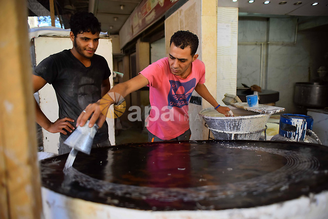 "An Egyptian vendor prepares a traditional sweets known as ""Konafa"" on the Muslim holy fasting month of Ramadan at market in Cairo, Egypt, on June 10, 2017. Ramadan is sacred to Muslims because it is during that month that tradition says the Koran was revealed to the Prophet Mohammed. The fast is one of the five main religious obligations under Islam. More than 1.5 billion Muslims around the world will mark the month, during which believers abstain from eating, drinking, smoking and having sex from dawn until sunset. Photo by Amr Sayed"