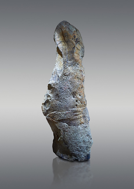 Late European Neolithic prehistoric Menhir standing stone with carvings on its face side. The remains of a representation of a stylalised male figure starts at the top with a long nose from which 2 eyebrows arch around the top of the stone. below this is a carving of a falling figure with head at the bottom and 2 curved arms encircling a body above. at the bottom is a carving of a dagger running horizontally across the menhir. the bottom is a carving of a dagger running horizontally across the menhir. Excavated from Piscina 'E Sali IV site,  Laconi.  Menhir Museum, Museo della Statuaria Prehistorica in Sardegna, Museum of Prehoistoric Sardinian Statues, Palazzo Aymerich, Laconi, Sardinia, Italy. Grey background.