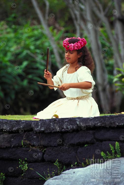 Young girl performing a noho (seated)  hula with kalaau sticks