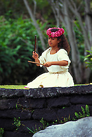 Young girl performing a noho (seated)  hula with kalaau sticks