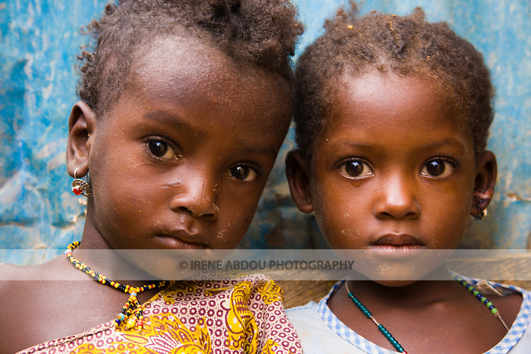 Two young Fulani children stand in front of a blue door in the small, rural village of Bele Kwara in southwestern Niger.   The Fulani people are traditionally nomadic, crisscrossing the Sahel with their cattle in search of water and green pastures.