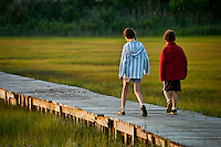 Kids walking on a boardwalk path through a salt marsh.