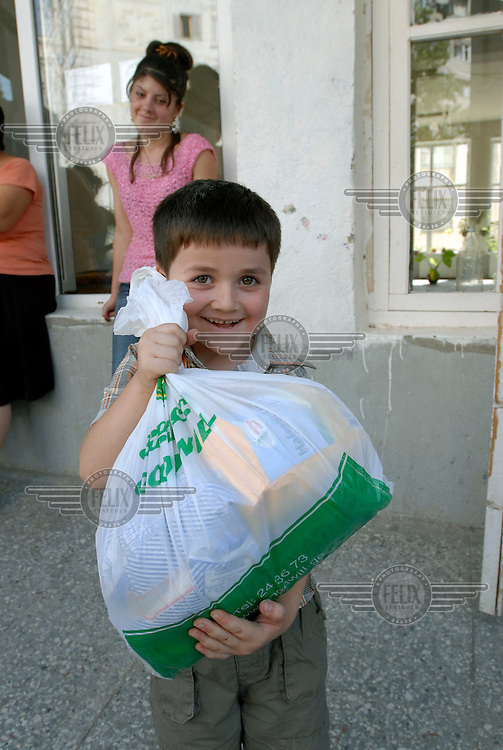 Six year old IDP Gocha Kokoshvili IDPs with supplies donated by Save the Children at a shelter in an old school.