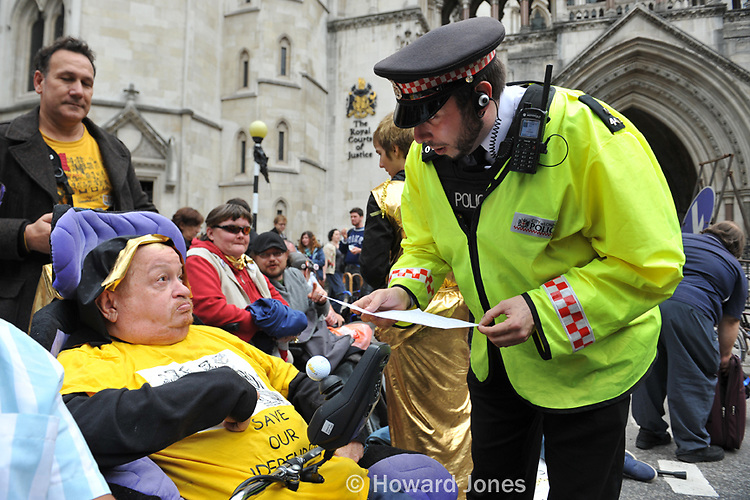 A disability rights activist is threatened with arrest for blocking the road during a legal aid cuts demonstration outside The Royal Courts Of Justice. Westminster, London 5th October 2013.