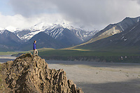 Hiker walks a rocky ridge along the Thorofare river, Denali National Park, Alaska