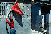 "China. Province of Beijing. Beijing. A young boy fixes near the public conveniences for men and women a chinese flag in a small alley of an old traditional town's quarter, called ""Hutong"". Chinese flag is on display for the feast of the first of may.  © 2004 Didier Ruef"