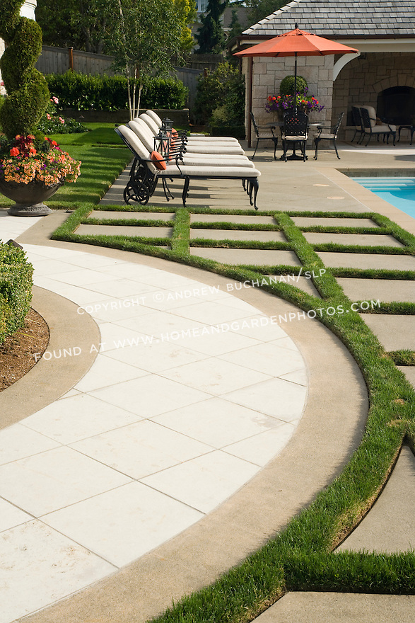 A curved and edged patio and a geometric pattern of concrete stepping stones and green grass strips define the edge of this poolside patio in suburban Seattle topped with pots of colorful summer annuals and high-end poolside furniture.