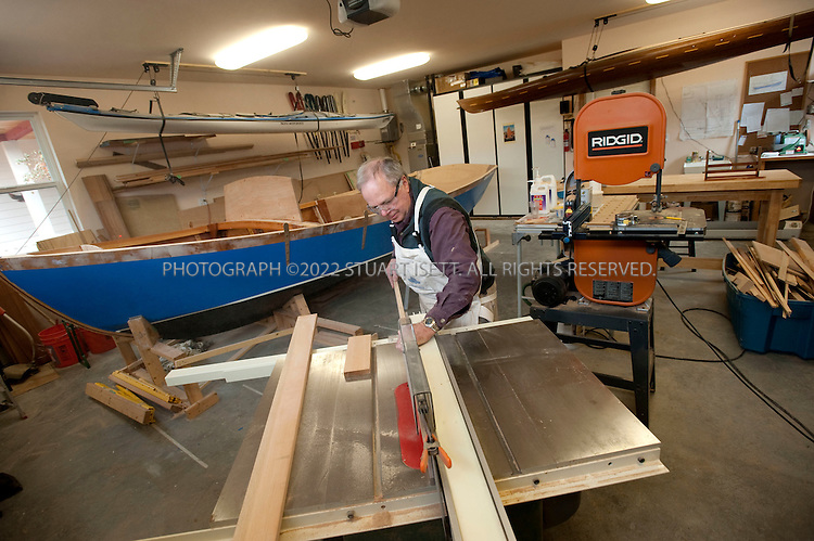 12/29/2009--Langley, WA, USA..Larry Cheek works in the garage of his home on Whidbey Island, WASH. on his latest wood boat, the 'Nil Desperandum'. The design is the Winter Wren II by Sam Devlin of Olympia, WA. and will be 18 feet long when completed...It's a gaff-rigged cruising sailboat made of plywood/fiberglass composite construction. The woods used are okoume plywood, khaya mahogany, white oak, and vertical-grain fir. Cheek started work on the boat in Oct. '08 and has a projected launch date of June '11. He estimates 1,500-2,000 hours of work will go into the boat...Here Mr. Cheek is trimming and installing thin fir planks on the inside of the hull to form the interior walls of the hull...©2009 Stuart Isett. All rights reserved.