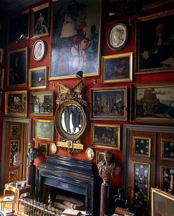 One wall of the double-height drawing room is covered in a collection of framed artwork