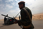 An armed rebel stands in the road to the city of Ajdabiya, Libya, March 24, 2011. Despite air strikes from Western war planes, which crippled Col. Muammar Qaddafi's military capability, the rebels seemed unable to advance and retake the city.