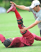Washington Redskins quarterback Robert Griffin III (10) lies on his back as a trainer works on his injured leg during the last day of OTAs at Redskins Park in Ashburn, Virginia on Thursday, June 6, 2013.<br /> Credit: Ron Sachs / CNP