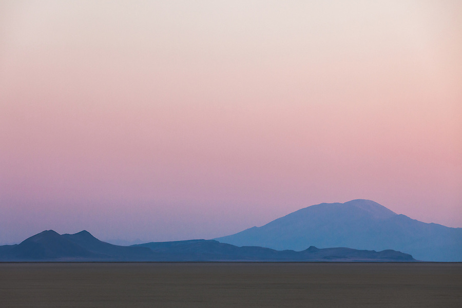 The distant hills glow a bluish-purple in the pastel colors of twilight seen from the Alvord Desert in Southeast Oregon.