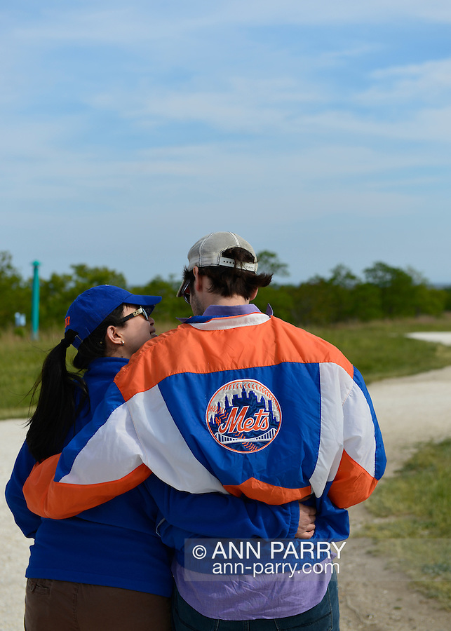 At Levy Park & Preserve, a young man, wearing a Mets baseball jacket, and a woman have their arms around each other as they face south toward the sky over Jones Beach where planes performed in the Bethpage New York Air Show. Many visitors watched the air show from the marshland park after several major parkways to the famous Long Island beach were closed when it filled to capacity.