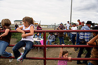 A small audience watches competitors ride a mechanical bull at the Mechanical Bull-A-Rama at the Whoa Arena in Valier, Montana, USA.  The event, organized by Janelle Nelson, was a benefit for local youth rodeo participants and the local food bank.