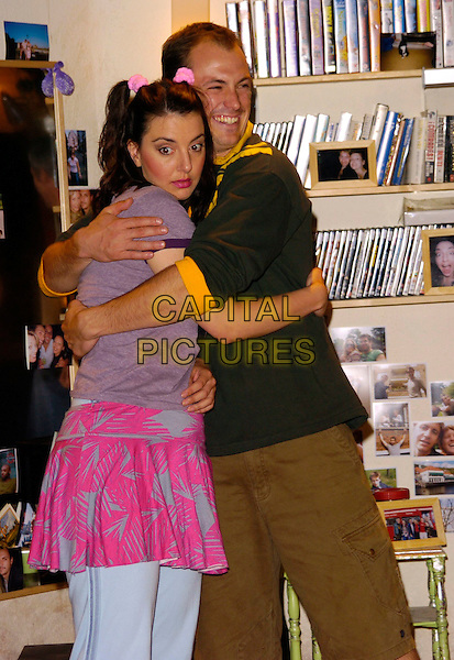 """REBECCA GETHINGS & BLAIR McDONOUGHBLAIR McDONOUGH.""""The Vegemite Tales"""" photocall, The Venue Theatre, London, UK..August 1st, 2006.Ref: CAN.half length shorts brown green yellow pink skirt hug embrace.www.capitalpictures.com.sales@capitalpictures.com.©Can Nguyen/Capital Pictures"""