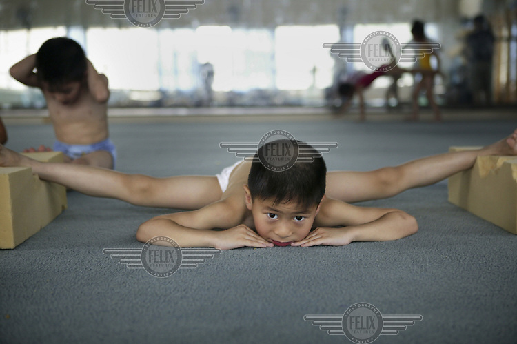 A first year student at the Children's Sport School in the Xuhui District of Shanghai. In order to build the strength and elasticity needed to become a top gymnast, the first year of training for these students involves mainly stretching. The Shanghai school selects 80 pupils each year, aged between five and six, and trains them for three and a half hours a day, six days a week. Only ten percent of the pupils will be accepted into the Shanghai Sports Institute to continue at a higher level, and only the top students from there will continue to the National School of Beijing to make up the Chinese team in the Olympic Games...