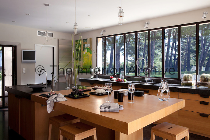 This contemporary kitchen benefits from a wall of windows and is furnished with wood and granite units and worktops