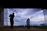Golfer watches his drive off one of the practice tees at a driving range in Westerville, OH, on a warm but wet day at the start of winter. The unusually warm weather attracted a number of golfers to enjoy the rare winter break from cold weather.