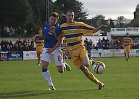 Lewis McLeod of Rangers and Martin McMullan go shoulder to shoulder in the Forres Mechanics v Rangers William Hill Scottish Cup 2nd Round match, at Mosset Park, Forres on 29.9.12.
