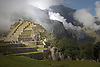 FOG RISES TO MEET THE INCA RUINS AT MACHU PICCHU,PERU