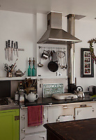 The kitchen wall above the Aga houses rows of kitchen utensils and a stainless steel extractor