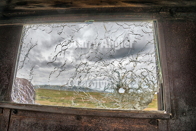 Window with bullet hole, 1940s Cleatrac crawler tractor with home-made cab, abandoned mid 20th century farm at the Traver Ranch, Carrizo Plain National Monument, San Luis Obispo County, Calif.