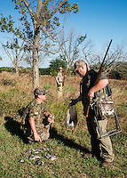 Patrick Bergmeier, his brother, Ramond Bergmeier, and his son Bret Bergmeier, age 16, during opening day of dove hunting season on Kansas State Wildlife fields near Wamego, Kansas, Sunday, September 1, 2013. Opening day is known for being a festive day of hunting with family and friends. <br /> <br /> Photo by Matt Nager