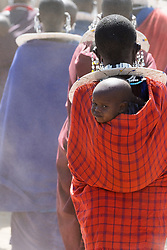 A young member of the Maasai People on his mother's back, Tanzania.