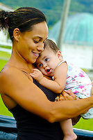 Hawaiian mother hugs her hapa Hawaiian baby daughter. Windward Community College observatory in background.