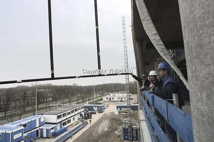 Foto: VidiPhoto..UTRECHT - In Utrecht werken bouwvakkers aan de constructie voor de skyboxen van stadion De Galgewaard. De metalen raamkozijnen voor de luxe skyboxen, die over een lengte van 84,50 meter geplaatst worden, werden dinsdag omhoog gehesen. Het voetbalpaleis van FC Utrecht wordt op dit moment uitgebreid van 13.500 naar 25.000 zitplaatsen. De werkzaamheden zijn vorig jaar november gestart. In 2004 moet alles gereed zijn. De verbouwing tot stadion annex sport/winkelcomplex kost 250 miljoen gulden. De provincie Utrecht schenkt 6 miljoen gulden. In ruil daarvoor krijgt het provinciebestuur de beschikking over een skybox.