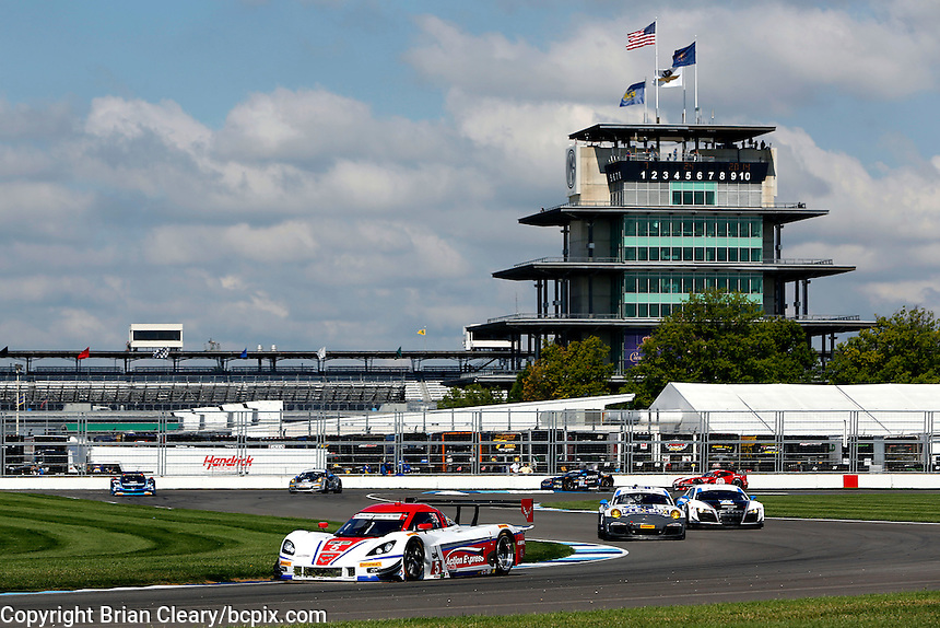 A pack of cars races past the Pagoda, Brickyard Grand Prix, Indianapolis Motor Speedway, Indianapolis, Indiana, July 2014.  (Photo by Brian Cleary/www.bcpix.com)