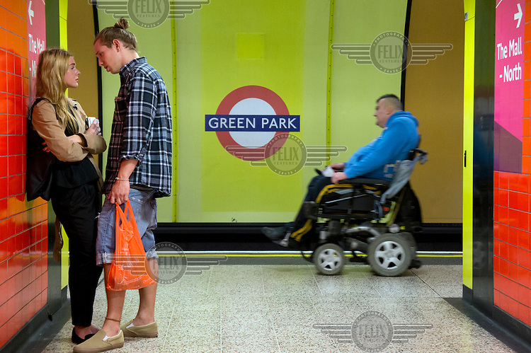 A couple engaged in an intimate conversation stand at the entrance to a platform on the London Underground in Green Park Station. Behind them a man in a wheelchair passes along the platform.