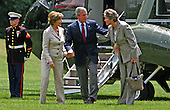 United States President George W. Bush and first lady Laura Bush talk briefly to Karen Hughes as they leave Marine One after flying from Camp David, Maryland.  They are on the South Lawn of the White House in Washington, DC on July 24, 2005.  <br /> Credit: Dennis Brack / Pool via CNP