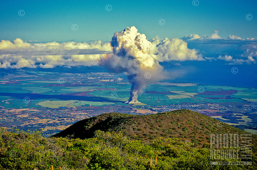 A sugarcane fire in Maui's Central Valley, with Maui's North Shore in the background. After 18 months the mature cane fields are set afire as part of the harvesting process.